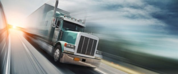 Green 18-wheeler Truck Driving On The Interstate Stock Photo