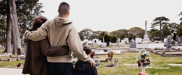 Father With Wife And Son At Cemetery Stock Photo