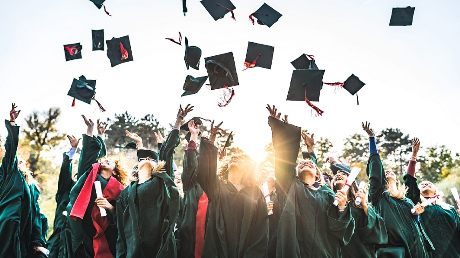College Graduates Tossing Hats In The Air Stock Photo