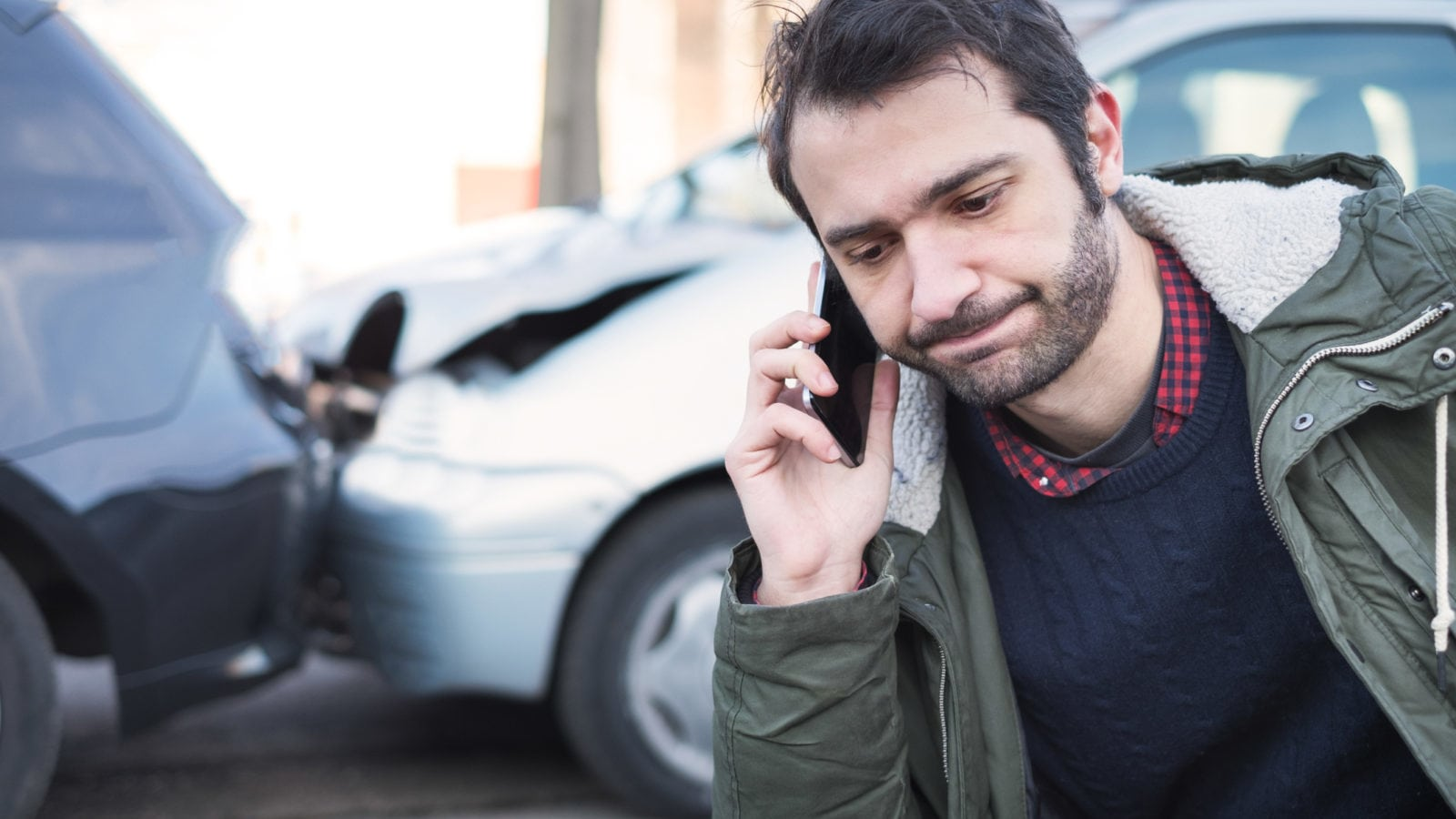 Young Man Calling Insurance Provider After Car Accident Stock Photo