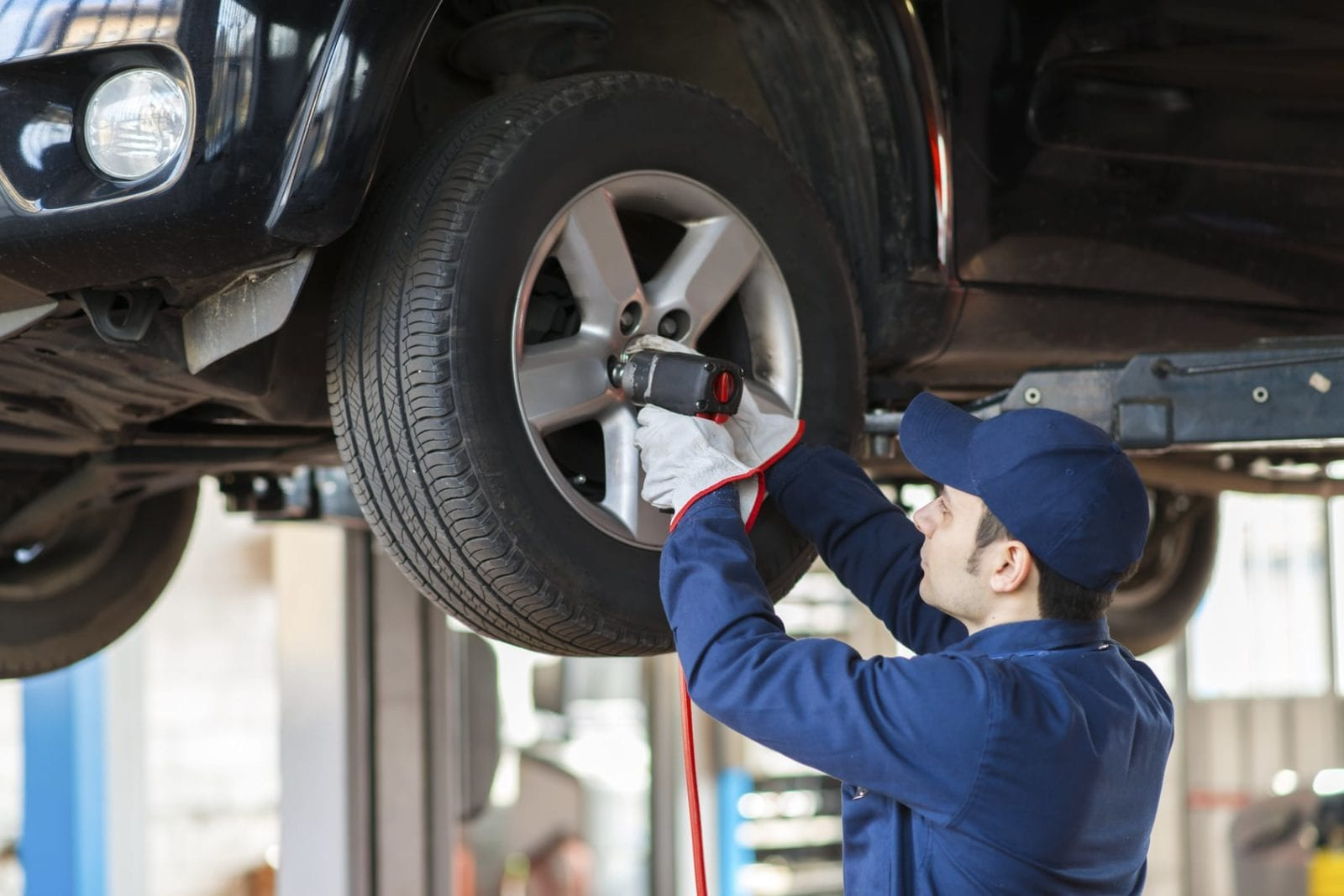 Mechanic Replacing A Tire On A Car Stock Photo