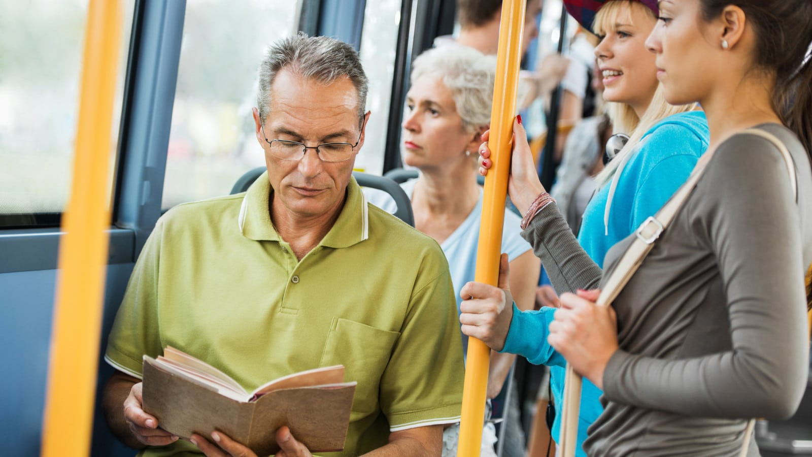 Senior Man Reading On A Public Bus Stock Photo