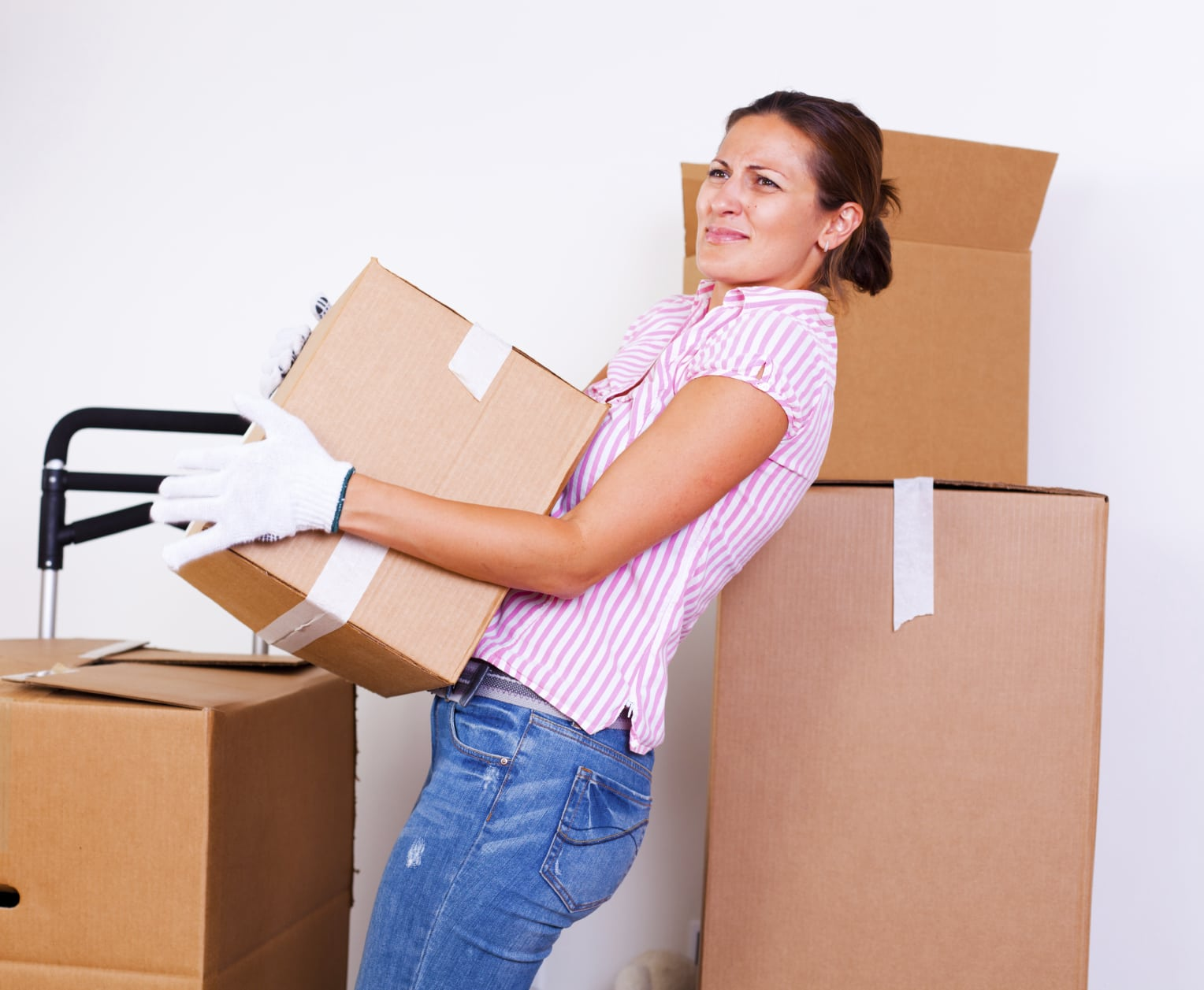 Young Woman Struggling With Lifting A Box Stock Photo