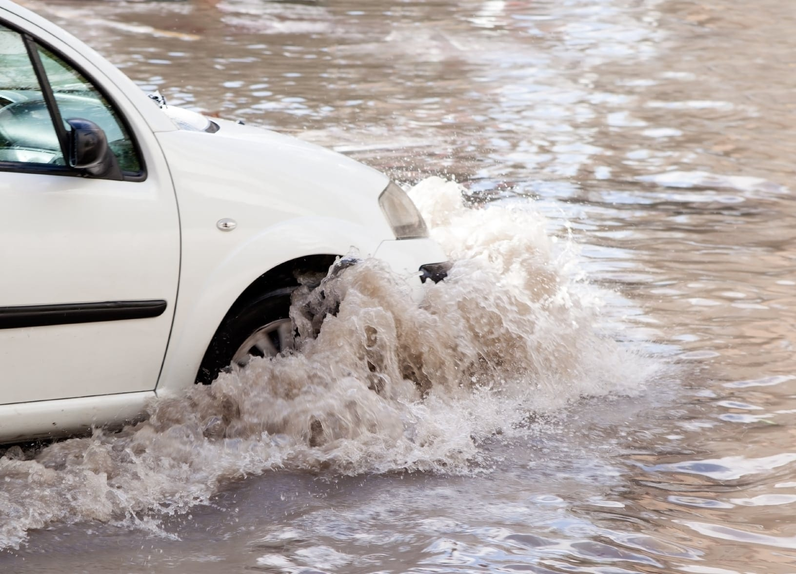 White Car Driving Into Flood Waters Stock Photo