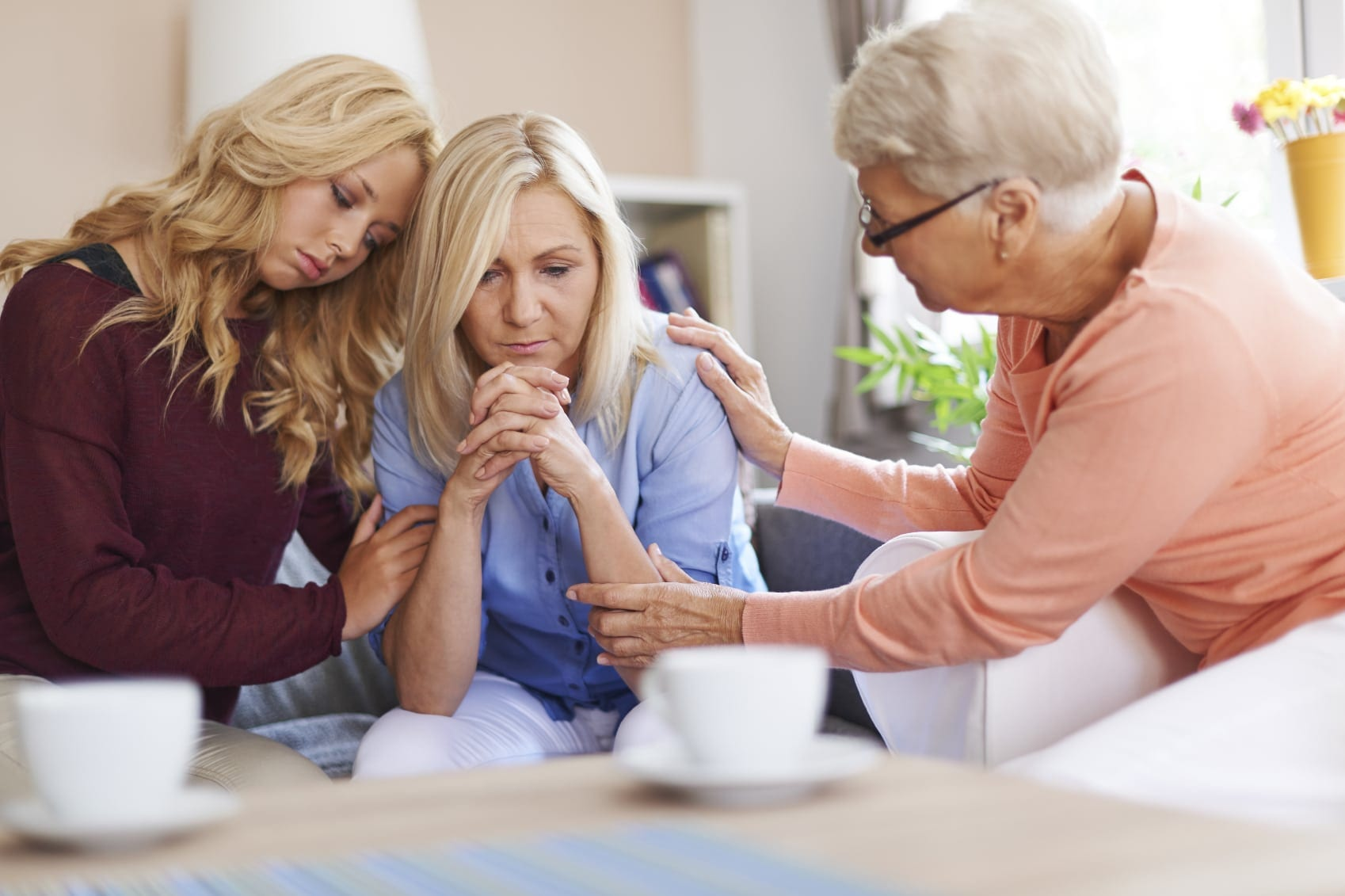 Mature Woman Being Consoled By Family Members Stock Photo