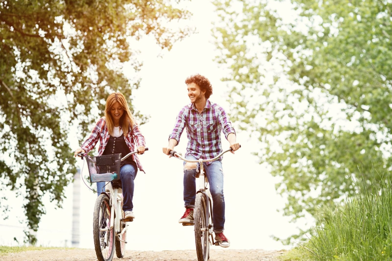 Young Couple Riding Their Bikes On A Dirt Road Stock Photo