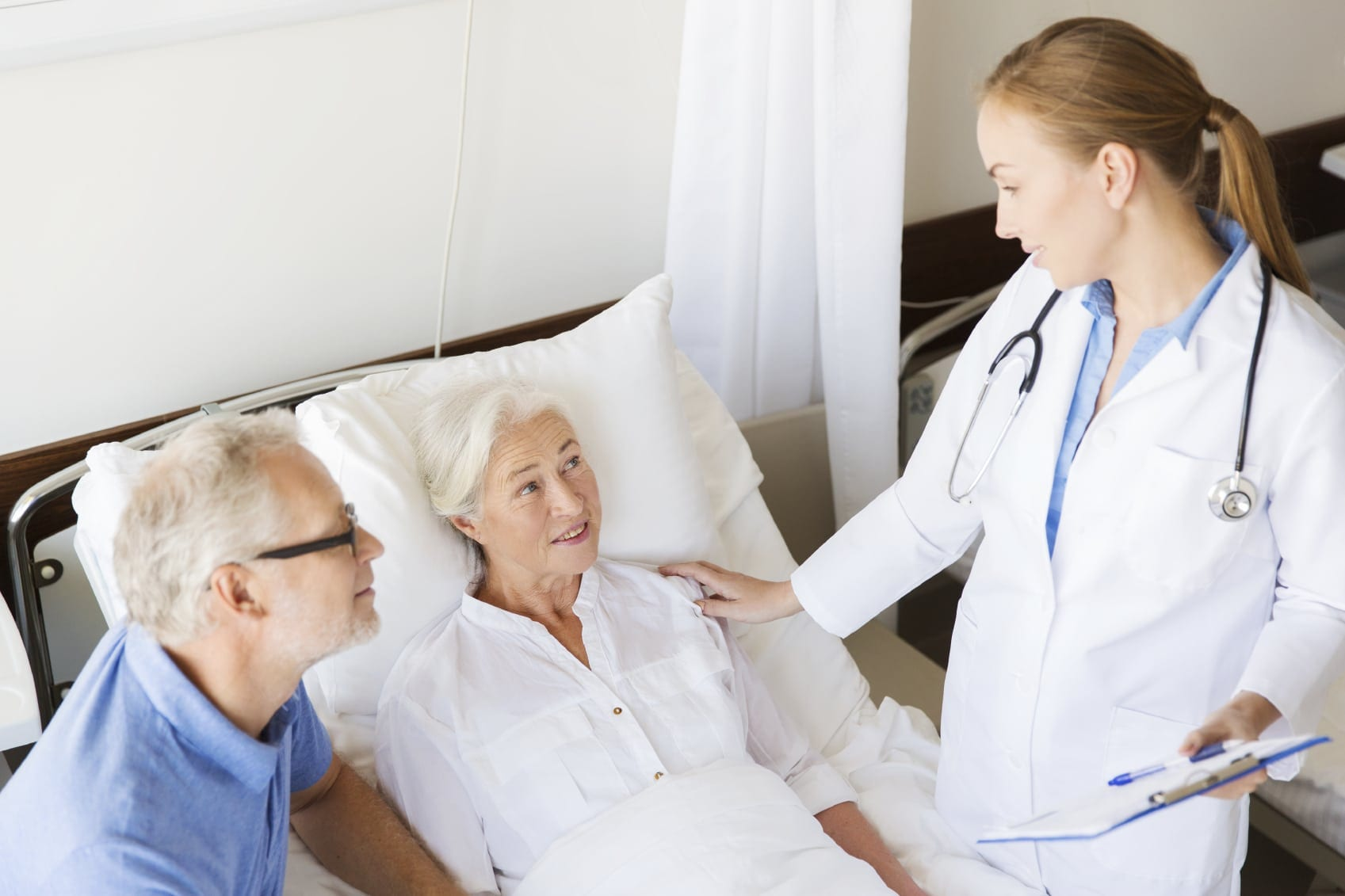 Doctor Consulting With Elderly Female Patient Stock Photo