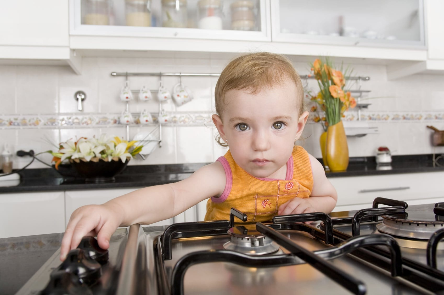 Young Child Touching The Switches On A Stove Stock Photo