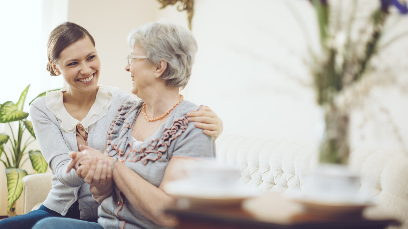Young Woman Consoling Elderly Woman Stock Photo