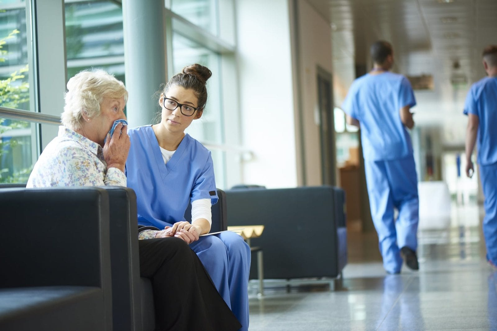Nurse Consoling Elderly Woman In A Hospital Hallway Stock Photo